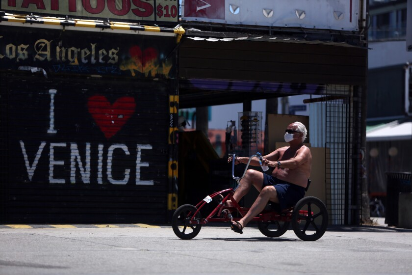 A man wears a mask while riding a tricycle along the boardwalk in Venice.