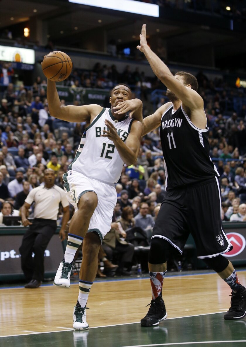 Milwaukee Bucks' Jabari Parker is fouled as he drives past Brooklyn Nets' Brook Lopez (11) during the second half of an NBA basketball game Saturday, Nov. 7, 2015, in Milwaukee. (AP Photo/Morry Gash)