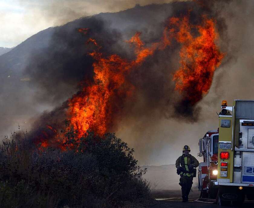 The state Supreme Court will hear arguments Tuesday in a dispute over whether California can impose rules on insurance companies aimed at bettering payouts for people who lose their homes in disasters. Above, a wildfire rages in 2003 near Lake Piru in Ventura County.