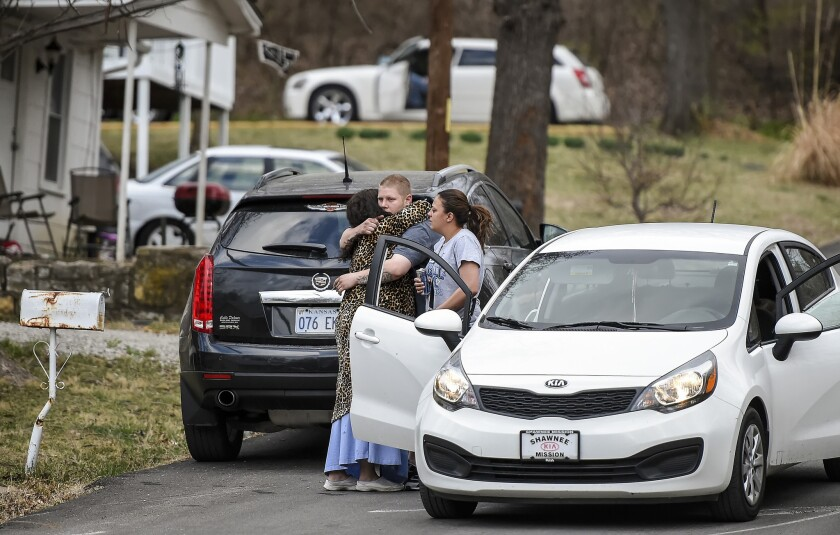 Victims' relatives embrace in front of the Kansas City, Kan., home where four people were shot to death on March 8. Pablo Antonio Serrano-Vitorino has been accused of the killings.