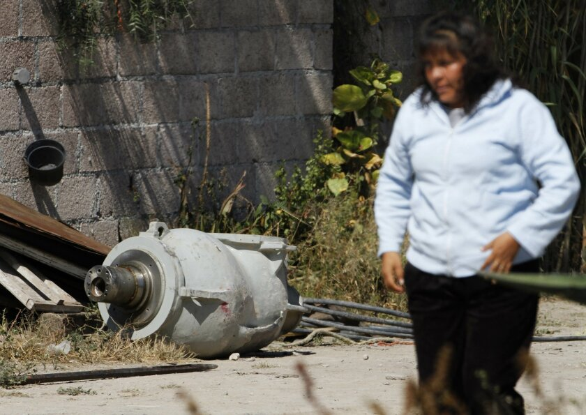 A woman walks near a radiation head that was part of a radiation therapy machine, in the patio of the family who found the abandoned radiation head in a nearby field in the village of Hueypoxtla, Mexico, Thursday, Dec. 5, 2013. Officials were engaged Thursday in the delicate task of recovering the stolen shipment of highly radioactive cobalt-60 abandoned in a rural field in central Mexico state. According to National Commission of Nuclear Safety and Safeguards, the radioactive source had been removed from the radiation head and was found nearby in an empty lot. (AP Photo/Marco Ugarte)