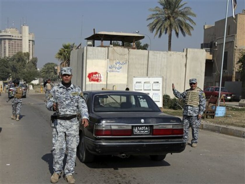 Iraqi police officers are seen at a checkpoint in central Baghdad, Iraq, Tuesday, Dec. 1, 2009. Fewer than 90 civilians were killed in violence in November in one of the lowest monthly death tolls in Iraq since the U.S.-led invasion in 2003, officials said Monday. (AP Photo/Karim Kadim)