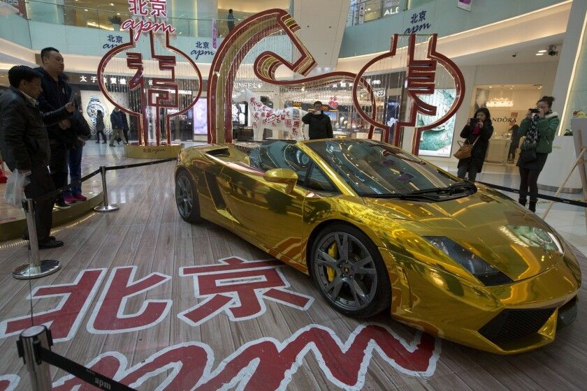 A gold Lamborghini sports car, with a price tag of $808,000, is displayed in a mall in Beijing.