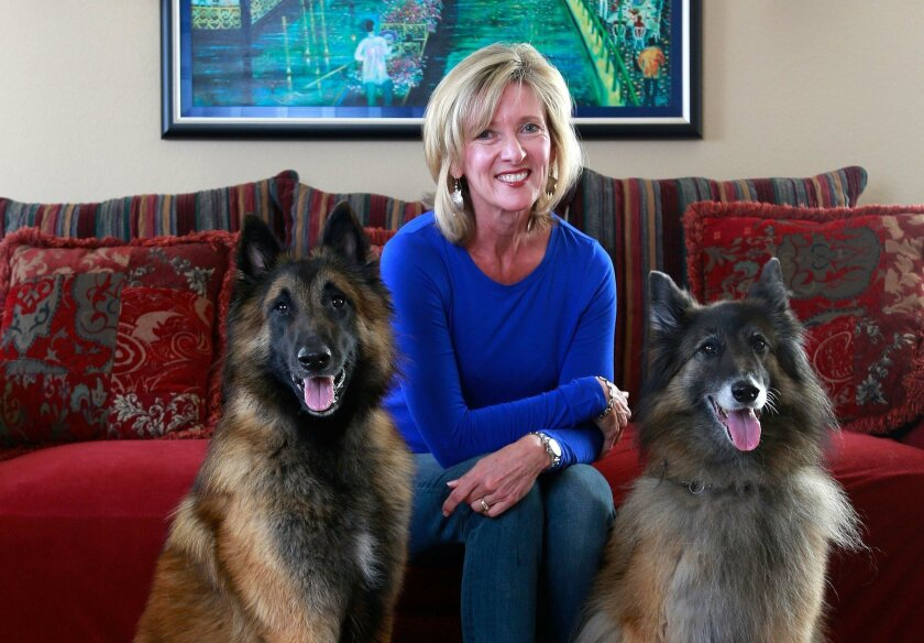 Dog trainer Laura Christiansen at her Carlsbad home with her two Belgian Tervuren dogs, Caden, left, and Grace, right.