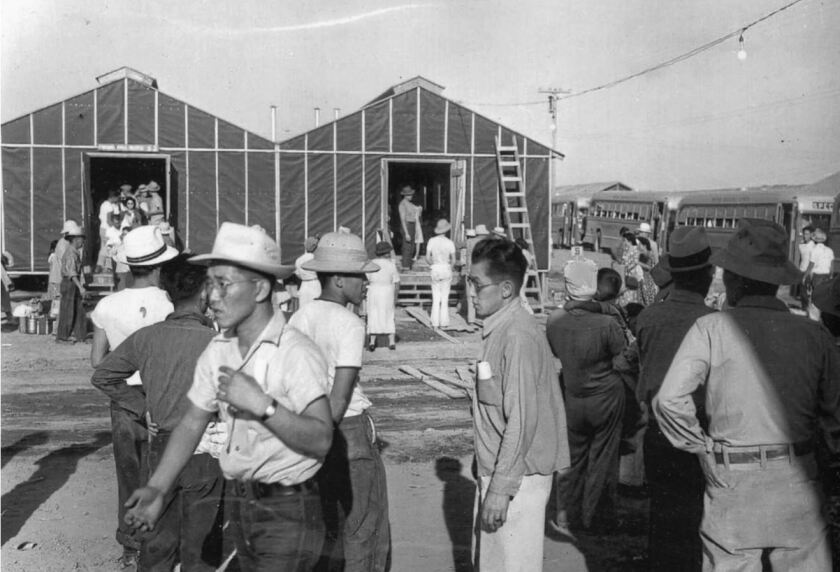 A scene from the Poston, the World War II Japanese American incarceration camp which detained most of the Japanese Americans living in Orange County, showing the barracks and arrival buses.