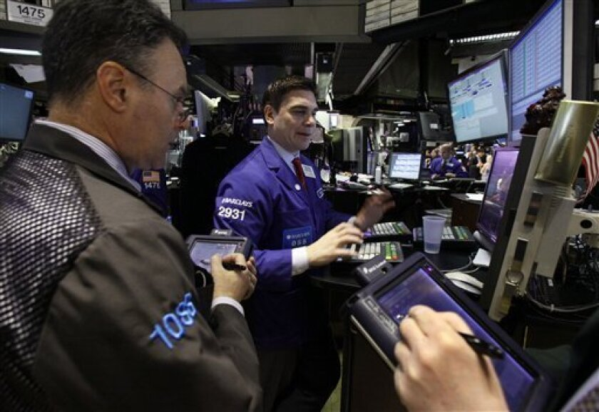 Specialist Robert Tuccillo, center, works with traders on the floor of the New York Stock Exchange Monday, April 9, 2012. Stocks are opening sharply higher, Wednesday, April 11, 2012, a day after their worst loss of the year. (AP Photo/Richard Drew)