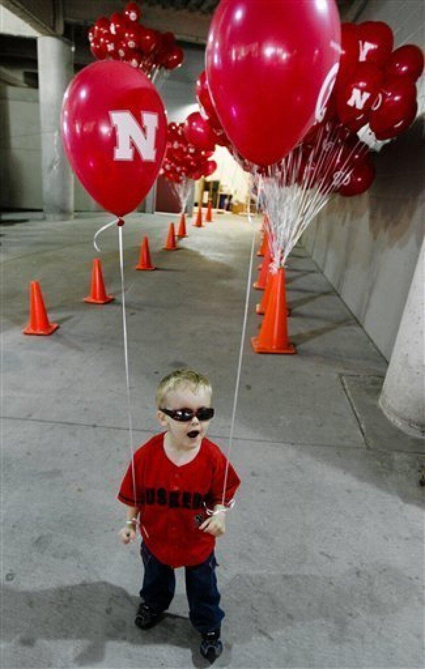 Four-year-old Benjamin Sealock, of Omaha, Neb., has Nebraska balloons tied to his wrists prior to an NCAA college football game between Nebraska against Idaho, in Lincoln, Neb., Saturday, Sept. 11, 2010. (AP Photo/Nati Harnik)