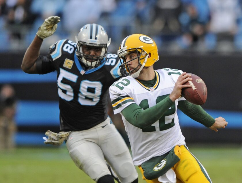 Green Bay Packers' Aaron Rodgers (12) scrambles as Carolina Panthers' Thomas Davis (58) pursues in the second half of an NFL football game in Charlotte, N.C., Sunday, Nov. 8, 2015. (AP Photo/Mike McCarn)