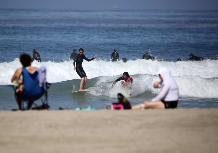 One day after Newport Beach opened up its beaches to recreational activities, dozens of surfers took to the water at the Newport Pier in Newport Beach on May 7.