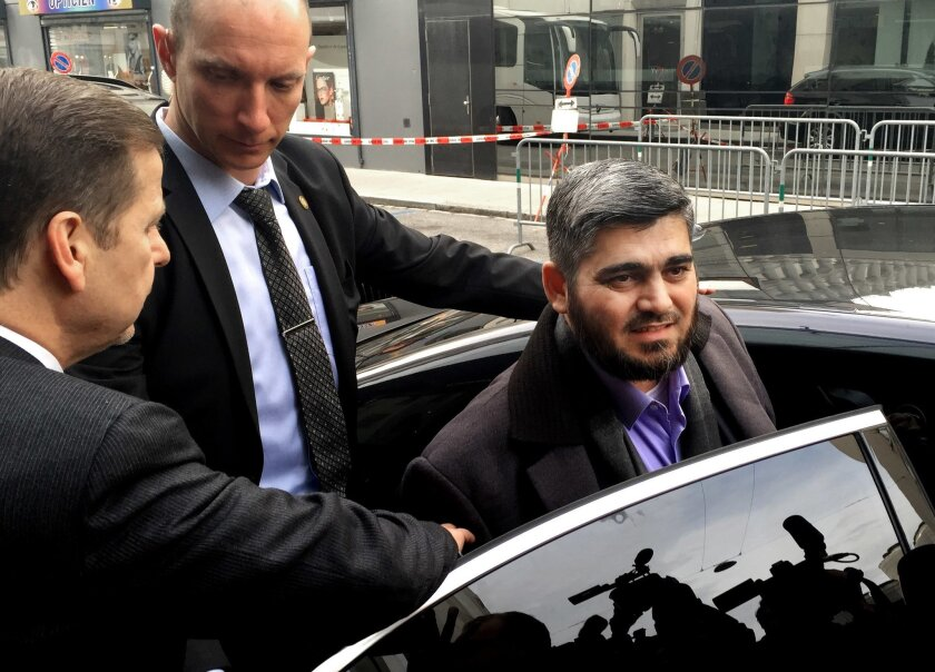 """FILE - In this Tuesday, Feb. 2, 2016 file photo, Army of Islam official Mohammed Alloush, gets in to a car heading to a meeting with the opposition's High Negotiations Committee, in Geneva, Switzerland. The Syrian opposition's chief negotiator to the peace talks has resigned saying the international community is not """"serious"""" about reaching a solution for the country's five-year war.(AP Photo/Bassem Mroue, File)"""