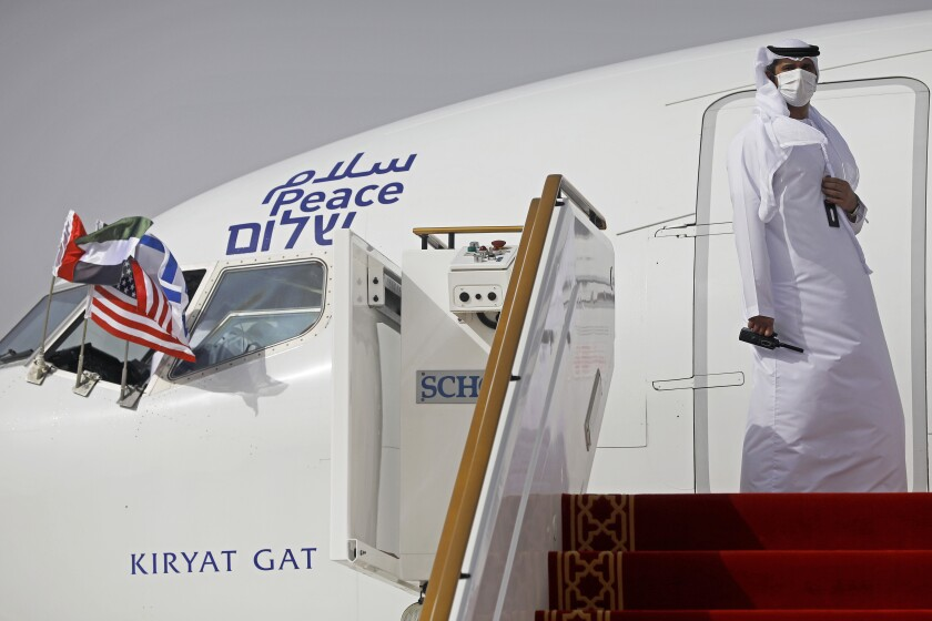An official stands at the door of an Israeli El Al airliner after it landed in Abu Dhabi, United Arab Emirates, Monday, Aug. 31, 2020. The Star of David-adorned El Al plane landed in Abu Dhabi after flying in from Israel, carrying a high-ranking American and Israeli delegation to Abu Dhabi in the first-ever direct commercial passenger flight to the United Arab Emirates. The Israeli flag carrier's flight Monday marks the implementation of the historic U.S.-brokered deal to normalize relations between the two nations. (Nir Elias/Pool Photo via AP)