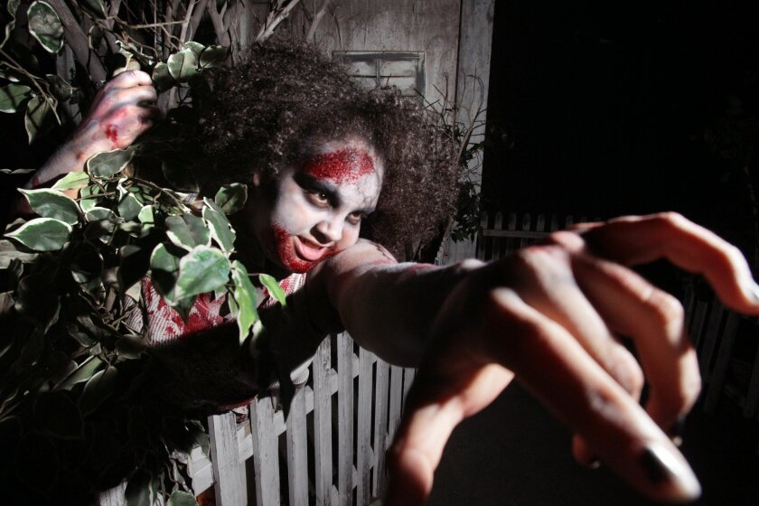 A ghoul reaches out to visitors passing through The House of Horror at The Scream Zone.