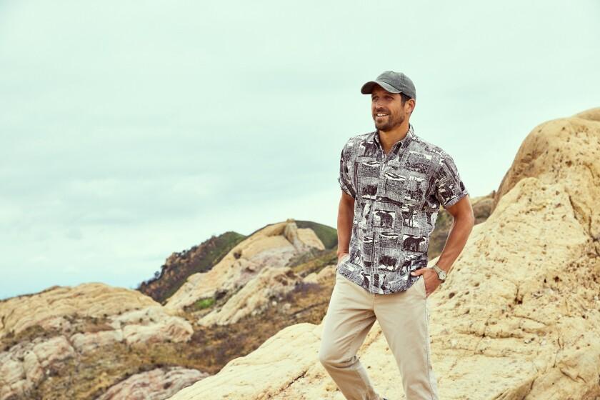 A man standing on rocks models Reyn Spooner's Yellowstone shirt.