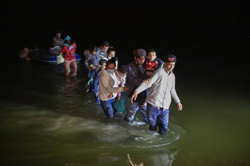 Migrantes, la mayoría centroamericanos, caminan por un río al llegar a la frontera en Roma, Texas