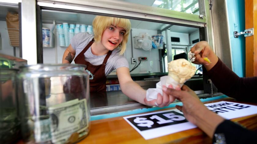 Caitlyn Faircloth, a worker with Molly Moon's Homemade Ice Cream, hands out free ice cream next to a tip jar, Monday, June 2, 2014, at a rally outside City Hall in Seattle celebrating the Seattle City Council's approval of a $15 minimum wage.