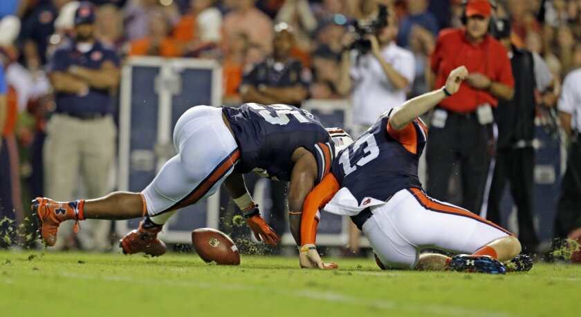 Auburn running back Peyton Barber (25) and quarterback Sean White (13) scramble to fall on a fumble during the first half of an NCAA college football game against Mississippi State, Saturday, Sept. 26, 2015, in Auburn, Ala. (AP Photo/Butch Dill)
