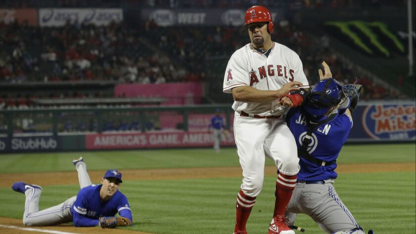 Toronto Blue Jays catcher Danny Jansen, right, tags out Los Angeles Angels' Albert Pujols at the pla