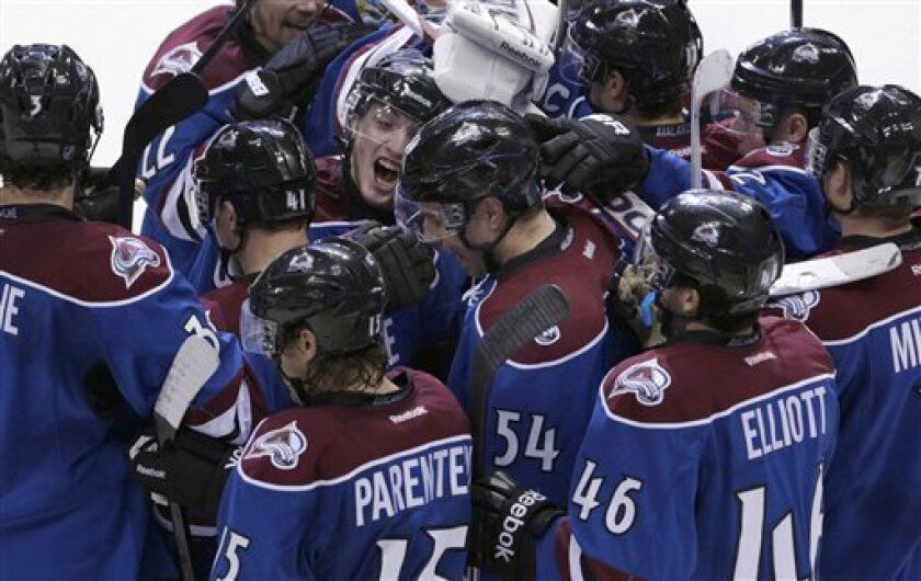Teammates congratulate Colorado Avalanche right wing David Jones (54) after he scored the game-winning goal in overtime against the St. Louis Blues in an NHL hockey game, Wednesday, Feb. 20, 2013, in Denver. Colorado won 1-0. (AP Photo/Joe Mahoney)