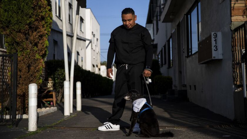 Maynor Garcia stands with the dog of his late brother Gabriel Dirzo, who L.A. County medical officials suspect died after snorting cocaine laced with fentanyl.