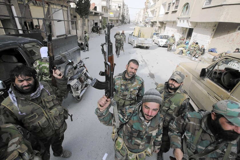 Pro-government forces stand on a street in the Syrian town of Yabroud. With Yabroud's capture, all the major towns along rebel supply lines from Lebanon are in government hands.