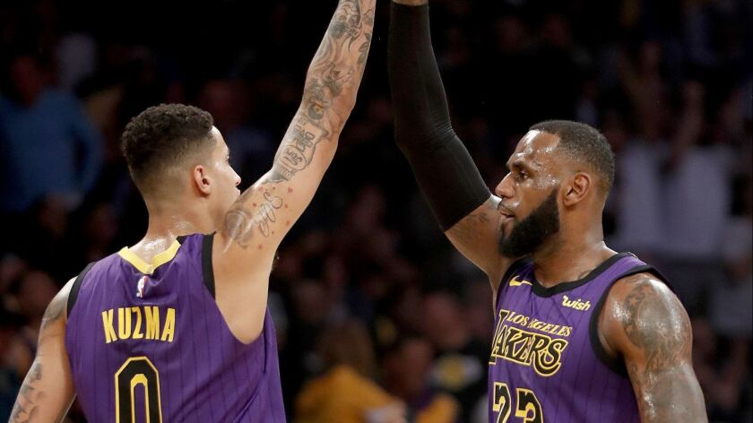 Lakers' Kyle Kuzma and LeBron James celebrate a basket in the first half on Wednesday at Staples Center.