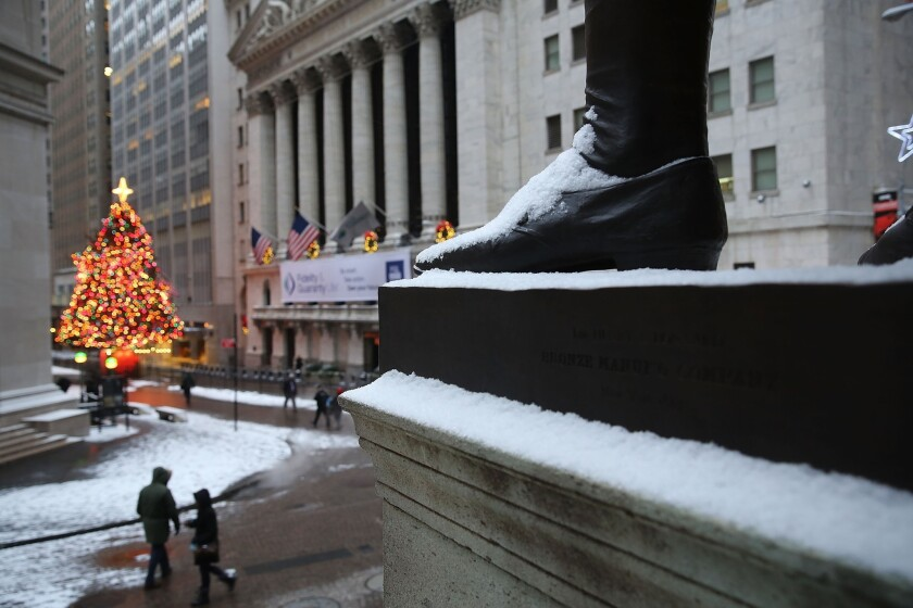 Snow dusts a statue of George Washington on Wall Street.