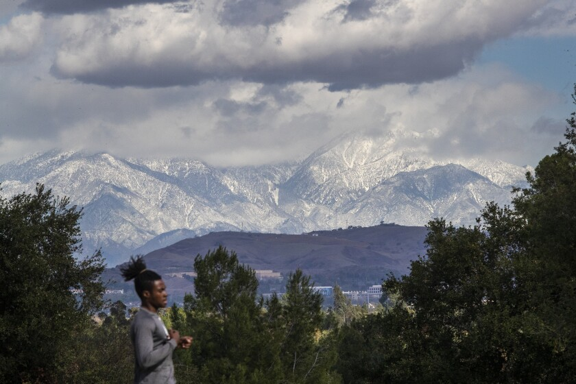 A runner has a little help from gusty winds while exercising with a view of snow-capped San Gabriel Mountains.