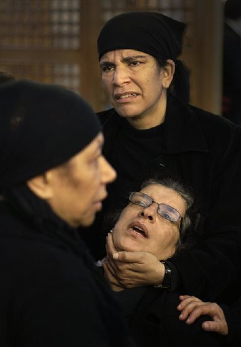 Egyptian Coptic Christian Ahlam Fawzy Saber, below-right, who lost two of her sisters and a niece in the blast, is comforted by relatives after collapsing from emotion following morning mass inside the Saints Church in Alexandria, Egypt, Sunday, Jan. 2, 2011. Grieving Christians, many clad in black, were back praying Sunday in the blood-spattered church where 21 worshippers were killed in an apparent suicide bombing, feeling betrayed by a government they say has not done enough to keep them safe. (AP Photo/Ben Curtis)
