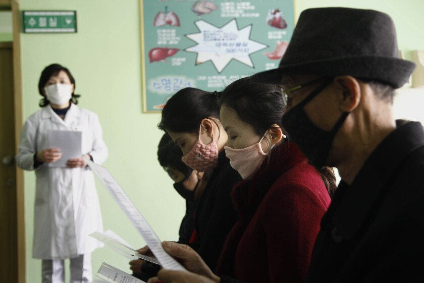 People review information explaining the coronavirus at the Pyongchon District People's Hospital in Pyongyang, North Korea.