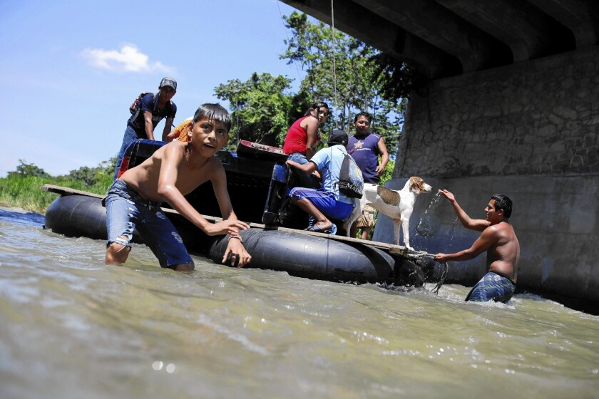 A raft carrying immigrants bound for the U.S. crosses the Suchiate River from Guatemala into Mexico.