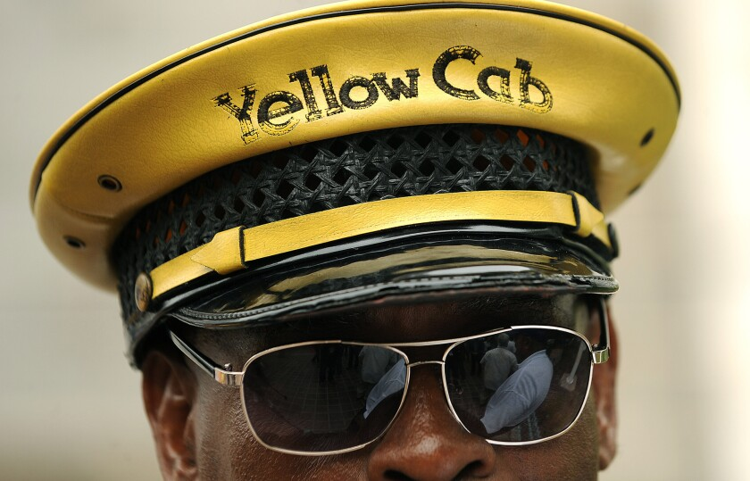 The chief taxi regulator in Los Angeles believes that three Web-based transportation services are indistinguishable from a traditional taxi company, and should cease operations immediately. However, while the companies - Uber, Sidecar and Lyft - may be distrupting the cab business, they're not operating cab companies and therefore don't fall under his purview. Above: Yellow Cab employee D'Mitch Davis stands outside City Hall in Los Angeles in protest of the rideshare apps that are hurting the taxi industry's business.