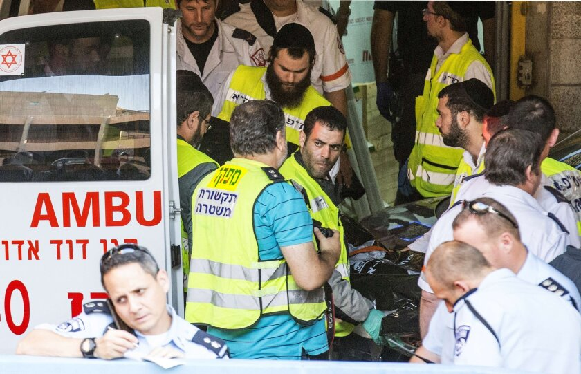 Israeli emergency services volunteers wheel into an ambulance the body of an Israeli who died during a stabbing attack in Tel Aviv on Thursday.