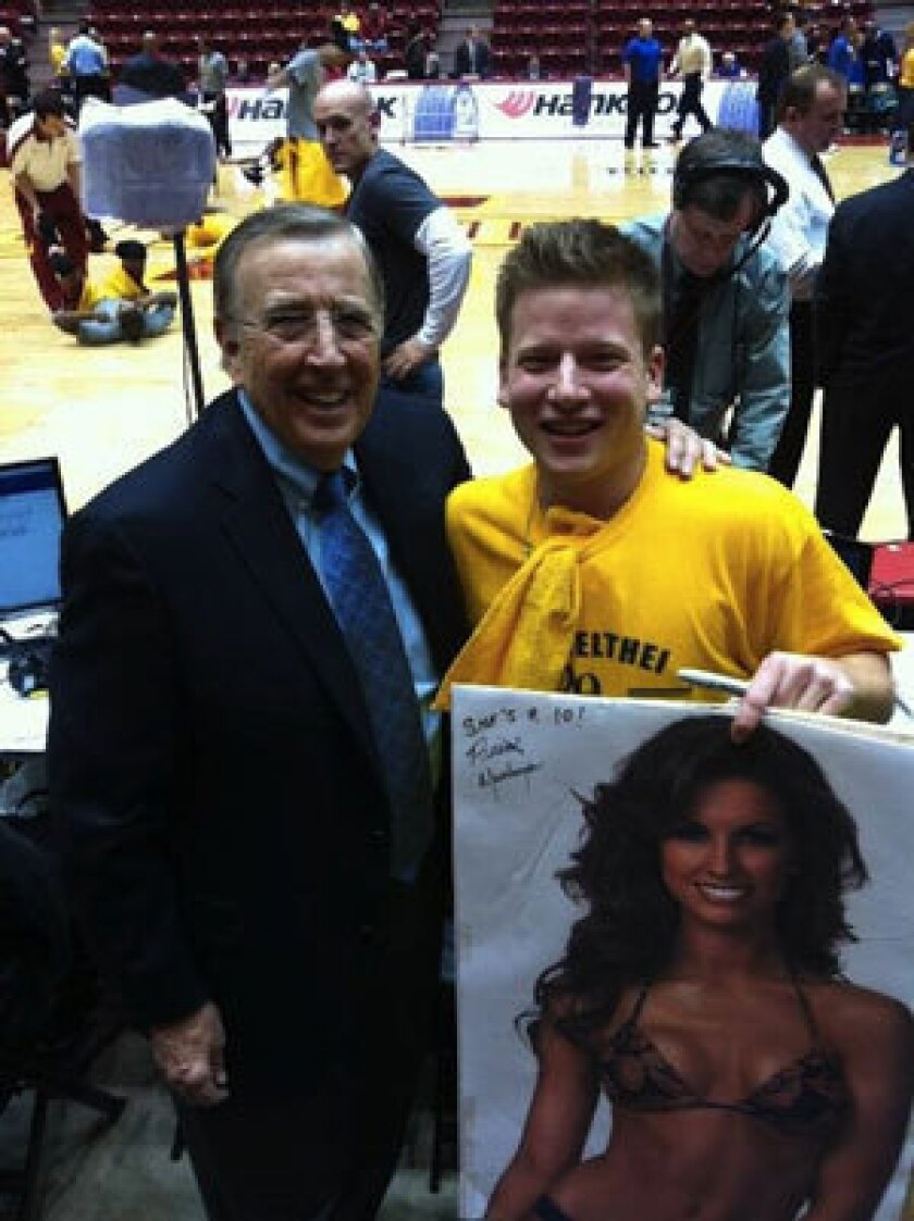Brent Musburger poses with a fan who after signing his Katherine Webb poster.