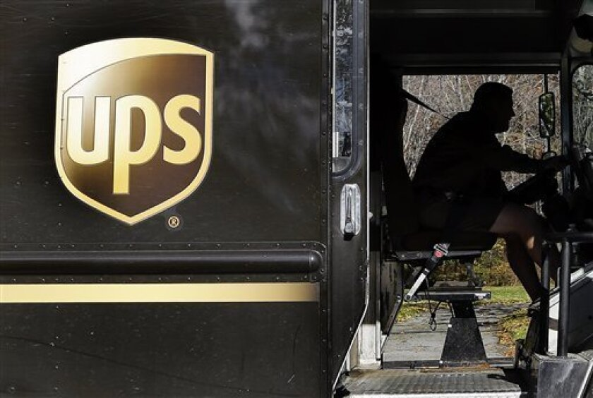 In this Monday, Oct. 22, 2012, photo, a UPS driver drives after a delivery in North Andover, Mass. In this Monday, Oct. 22, 2012, photo, a UPS driver makes a delivery in North Andover, Mass. UPS said Tuesday, Oct. 23, 2012,  its third-quarter earnings sank on a huge penalty to withdraw from a pensi