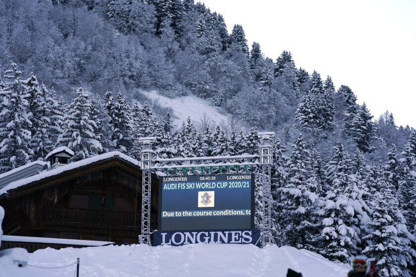 A giant screen reports that an alpine ski, women's World Cup giant slalom was cancelled due to course conditions following strong winds, in Courchevel, France, Saturday, Dec. 13, 2020. (AP Photo/Giovanni Auletta)