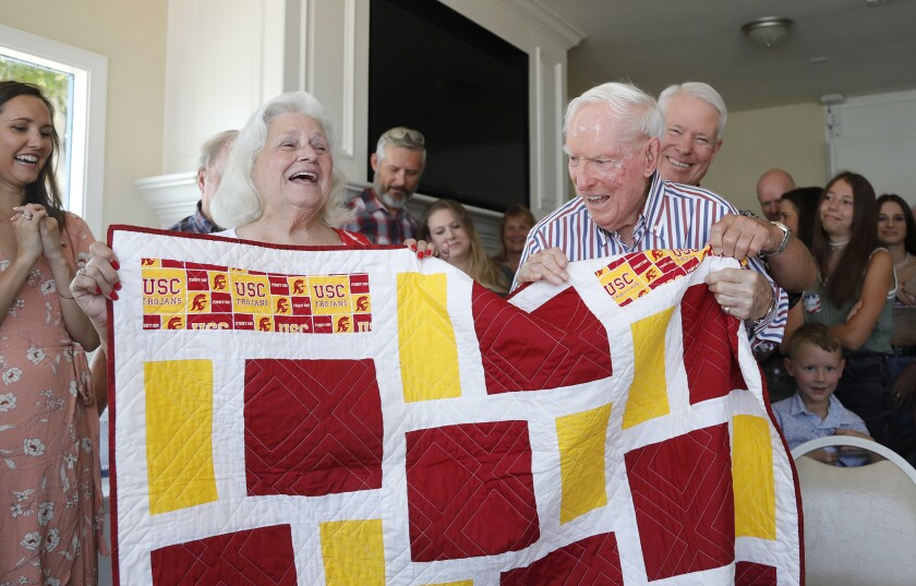 Barbara Winkler of SoCal Quilts of Valor, left, surprises Joseph King with a quilt  during his 100th birthday party.