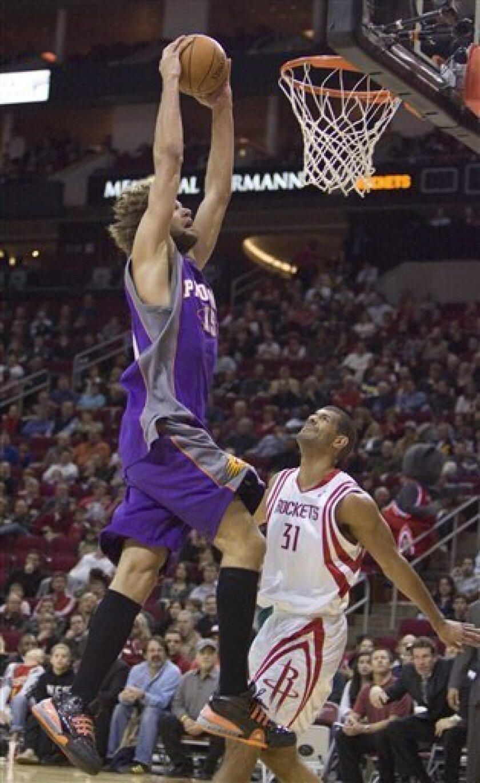 Phoenix Suns center Robin Lopez (15) scores over Houston Rockets' Shane Battier (31) during the first quarter of an NBA basketball game Sunday, Jan. 31, 2010, in Houston. (AP Photo/Steve Campbell)