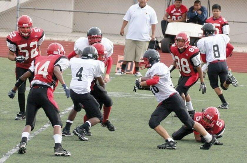 La Jolla freshman #4 Eric Timms makes a block as his teammate carries the ball. Photo: Susie Talman