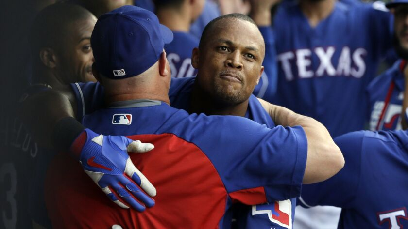 The Texas Rangers' Adrian Beltre, center, receives hugs in the dugout after hitting a three-run home run against the Angels last July.