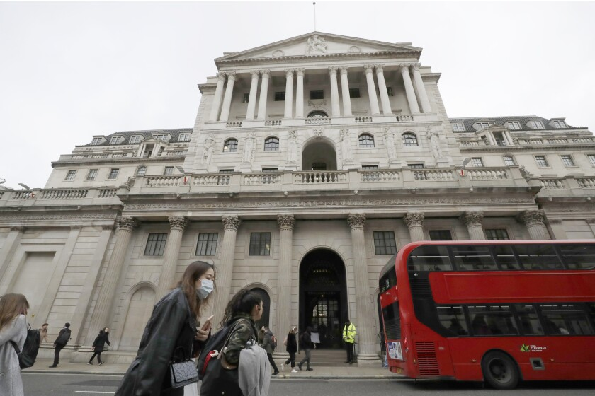 FILE - In this Wednesday, March 11, 2020 file photo, pedestrians wearing face masks pass the Bank of England in London. The Bank of England has kept its main interest rate at the record low of 0.1%. In a statement Thursday, June 24, 2021 accompanying its decision, the bank's rate-setting Monetary Policy Committee voted unanimously to keep borrowing rates unchanged. (AP Photo/Matt Dunham, File)