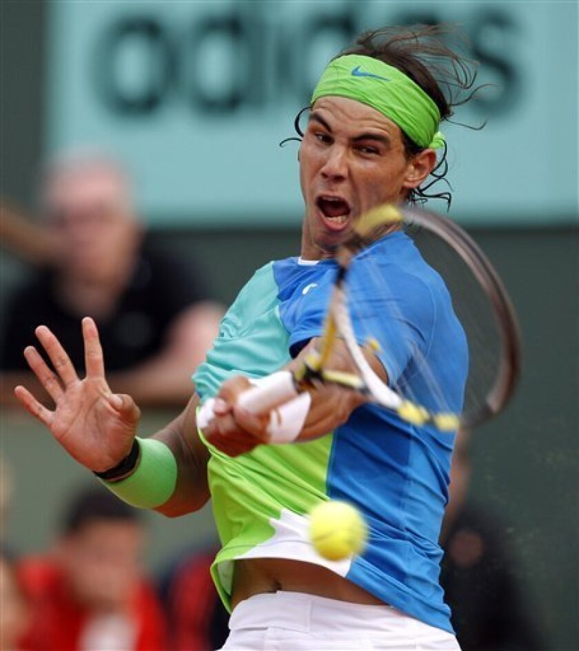 Spain's Rafael Nadal returns the ball to compatriot Nicolas Almagro during their quarterfinal match for the French Open tennis tournament at the Roland Garros stadium in Paris, Wednesday June 2, 2010. (AP Photo/Christophe Ena)