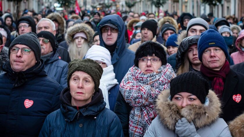 People watch the funeral of the slain mayor of Gdansk, Pawel Adamowicz, on a giant screen Jan. 19 outside St Mary's Basilica in Gdansk, Poland.