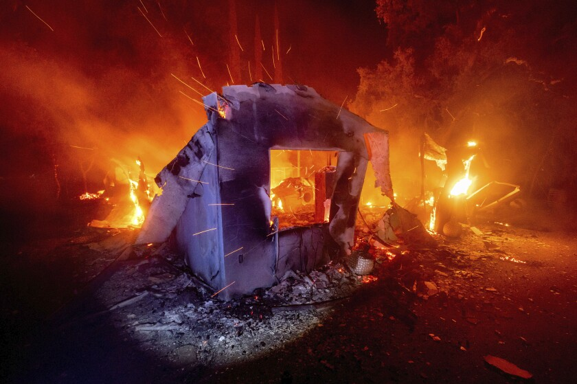 Flames from the LNU Lightning Complex fires consume a home in unincorporated Napa County, Calif.
