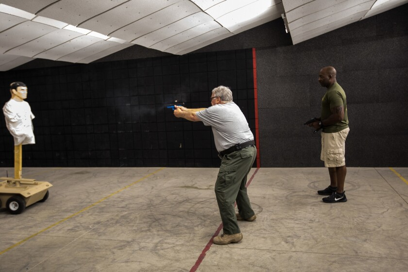 Howard Buffett, center, and Elgin Hawthorne, a deputy sheriff at the Macon County Sheriff's Office, demonstrate a simulation June 30, 2017, at the Grant Farm Training Facility, which trains police in deescalation and use of force, in Decatur, Ill.