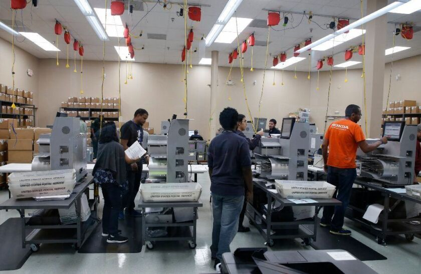 Florida elections workers feed ballots into tabulation machines at the Broward County supervisor of elections office in Lauderhill as three close midterm election races for governor, senator and agriculture commissioner are headed to recount.