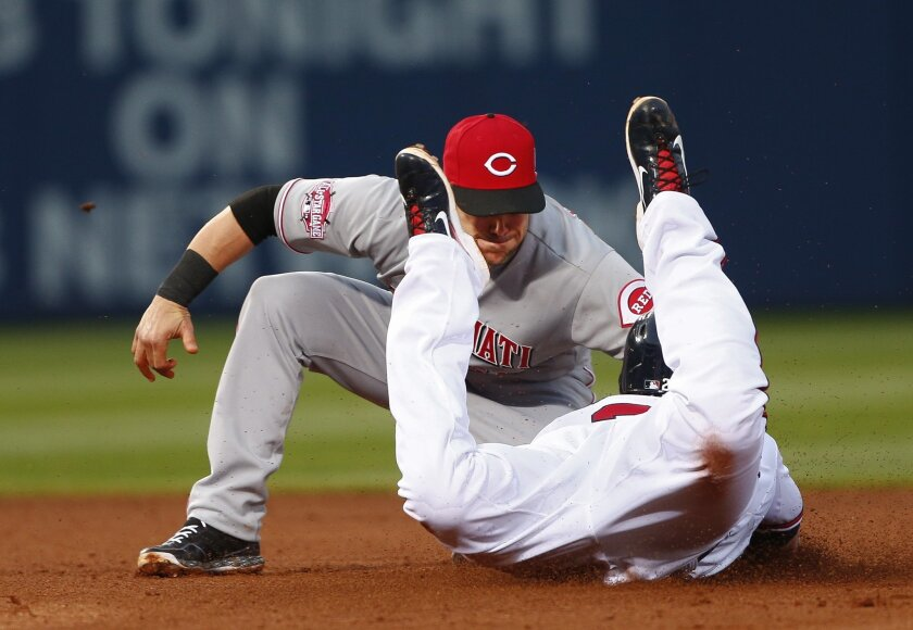 Atlanta Braves' Chris Johnson (23) is tagged out by Cincinnati Reds second baseman Skip Schumaker (55) as he attempts to second second base in the fifth in the inning of a baseball game  Thursday, April 30, 2015, in Atlanta. Cincinnati won 5-1. (AP Photo/John Bazemore)