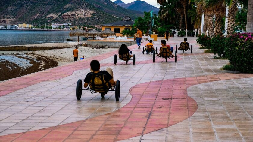 Children weave on trikes on La Paz's Malecón, which is considered one of the most beautiful boardwa