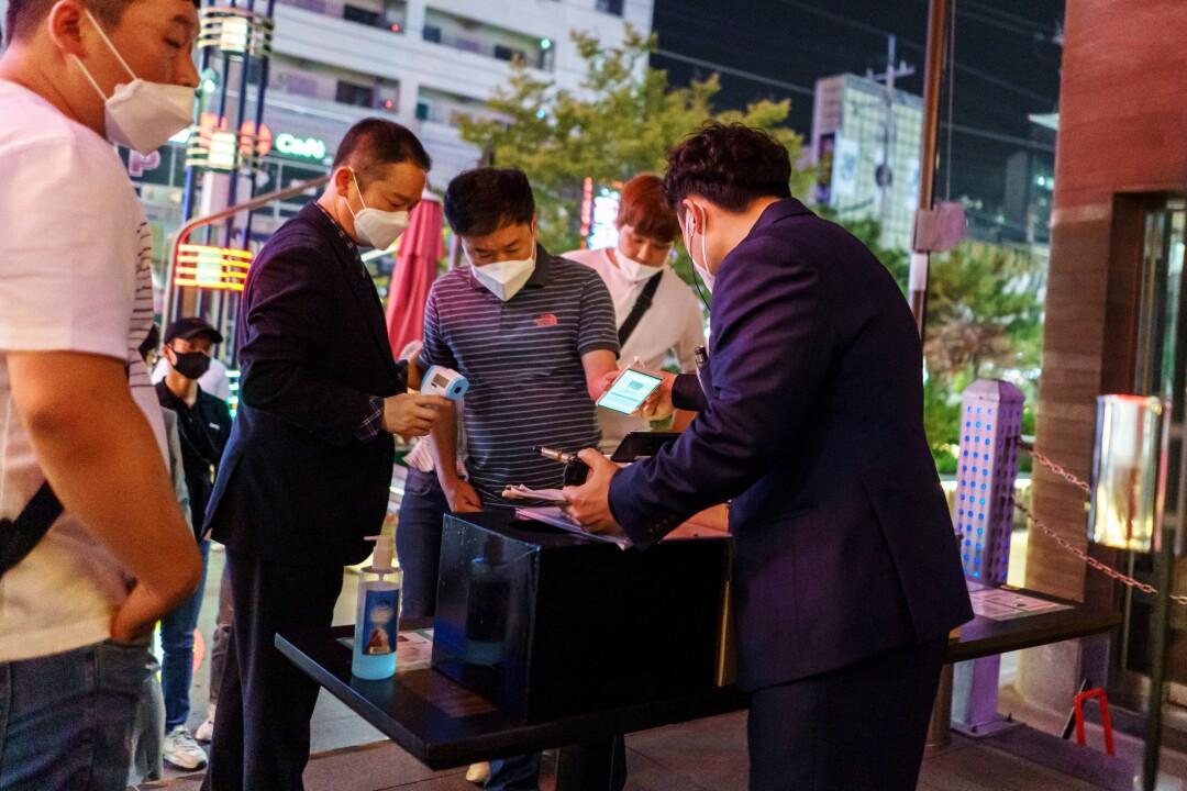 Bouncers register customers via QR codes on their smartphones.
