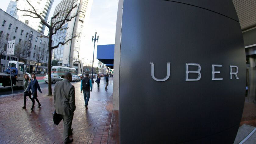In this photo taken Tuesday, Dec. 16, 2014, people go past the headquarters of Uber in San Francisco