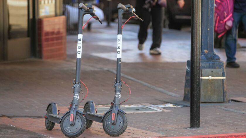 Two Bird scooters were parked on the sidewalk at E Street and 4th Avenue in Downtown San Diego in early March. The company's CEO says that the emerging bikeshare industry should police itself to be good neighbors.